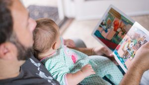 A father seated in an armchair reads a picture book to the baby on his lap