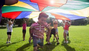 A group of children play under a colorful parachute in a green field on a bright, sunny day