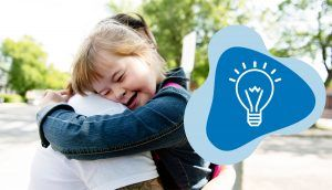 """A girl with Down's Syndrome smiles and rests her head on a woman's shoulder, with the blue """"Learn"""" icon in the bottom right"""