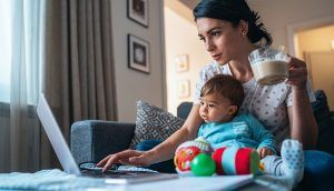 A mother holds her coffee as she works on a laptop with a baby seated on her lap