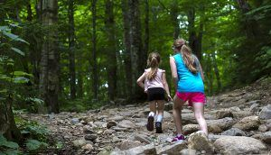 An older and younger girl are running through a rocky clearing in the woods.