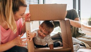 A smiling boy climbs through an open cardboard box lying on its side as a man and woman look on.