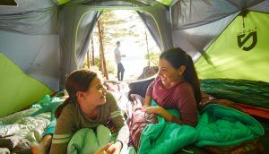 A woman and girl smile and laugh together in a tent as a man can be seen going for a walk outside.