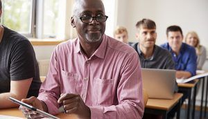 An older man is seated at the front of a class of adult learners, holding a clipboard