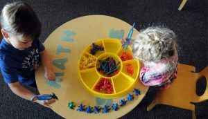 """One child sits and one child stands at a round table labeled """"MATH,"""" playing with toys."""