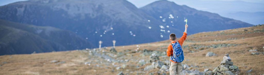 Young boy blowing bubbles while hiking at Mount Washington State Park, New Hampshire