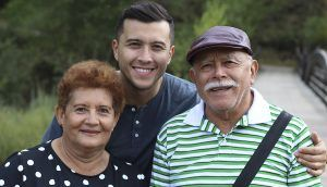 An older man, older woman, and younger man look forward and smile outside