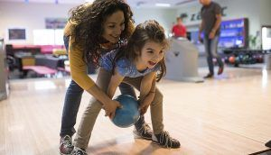 In a bowling alley, a woman helps a young girl roll a ball down the lane.
