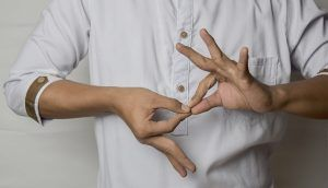 A person with only the middle of the body visible, makes a gesture with both hands.