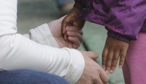A seated adult's hands holding the hands of a small child standing in front.
