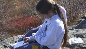Girl wearing a sweatshirt sits on a rock outside coloring on a clipboard