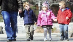 An adult and three small children hold hands as they walk together