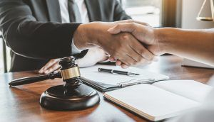 An attorney shakes hands with a client seated on the opposite side of a desk