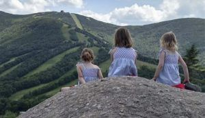 Three girls are seated on a small hill, looking out at the mountains