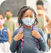 Young girl wearing a mask while attending school