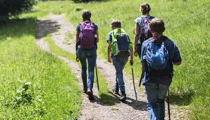 Children walking on hiking path with adult on a sunny day